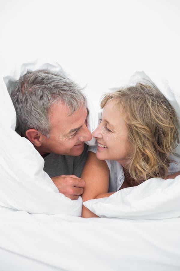 Милой пары постаретые серединой под одеялом стоковые изображения