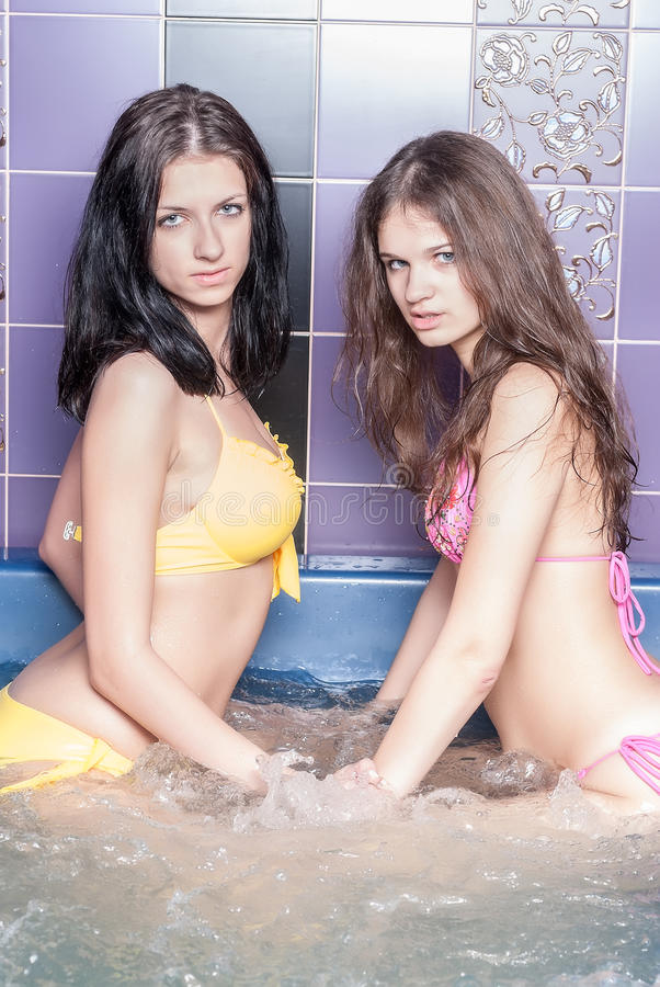 Милые девушки в ванне массажа стоковые фотографии rf