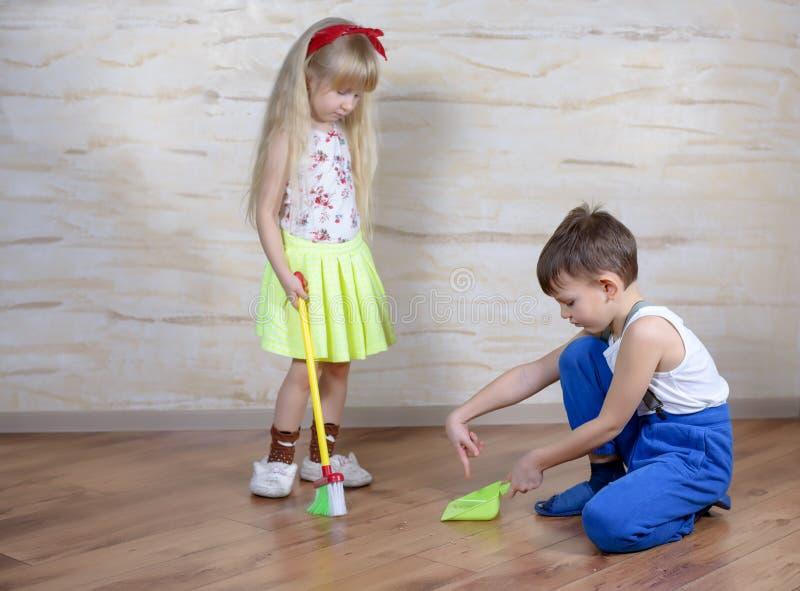 Милые дети используя веник и dustpan игрушки стоковая фотография rf