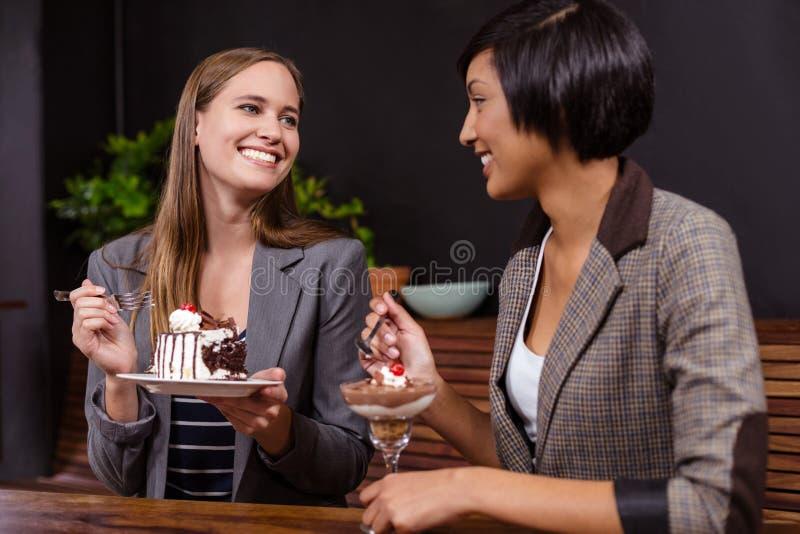 Милые женщины есть десерты стоковое фото rf