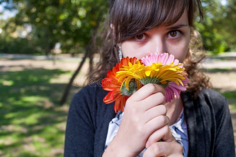 Милые женщины пахнуть пуком цветков стоковые изображения rf