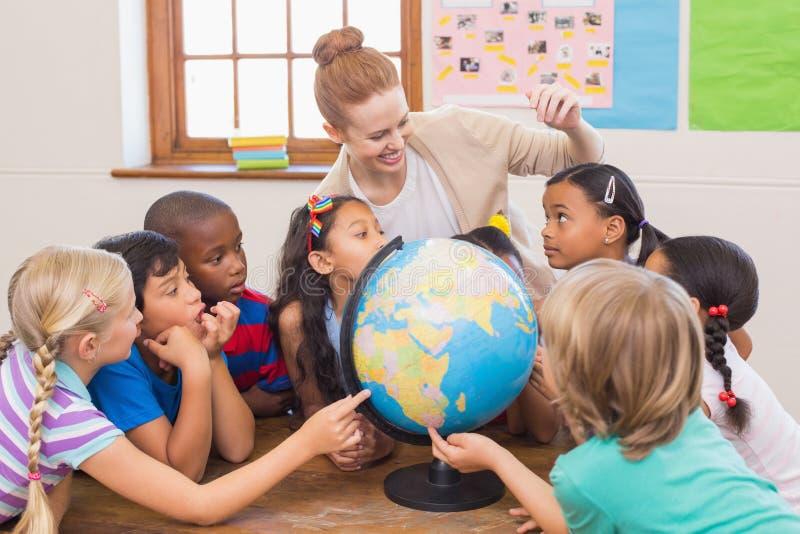Милые зрачки и учитель в классе с глобусом стоковые изображения