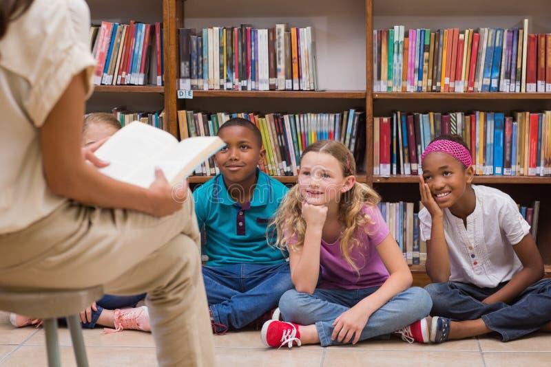 Милые зрачки и учитель имея класс в библиотеке стоковое изображение