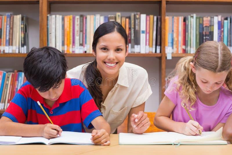 Милые зрачки порции учителя в библиотеке стоковое фото