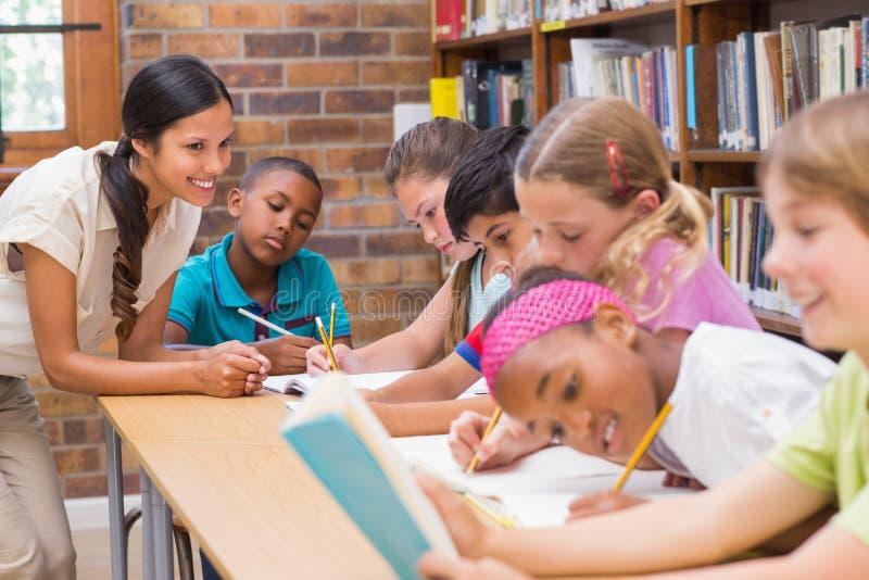 Милые зрачки порции учителя в библиотеке стоковое изображение rf
