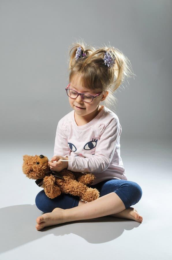 Милые игры девушки в докторе обрабатывают плюшевый медвежонка на сером ба стоковые фото