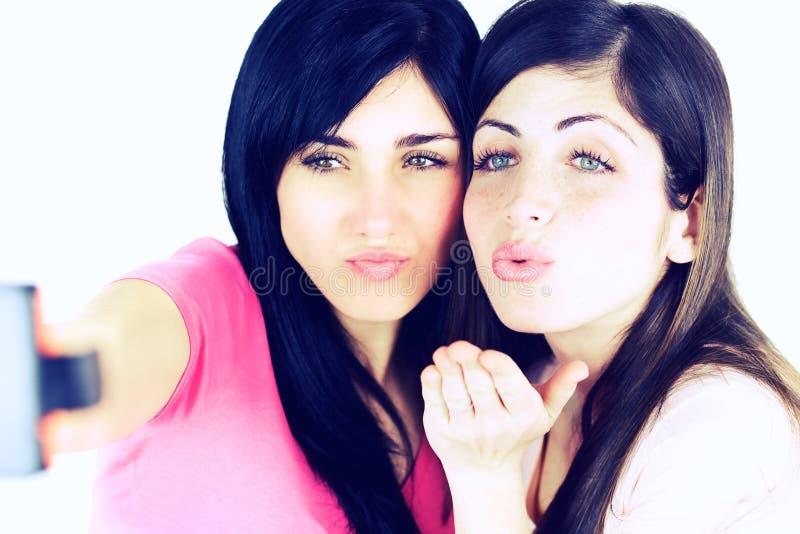 Милые красивые девушки дуя поцелуй принимая selfie стоковое изображение rf