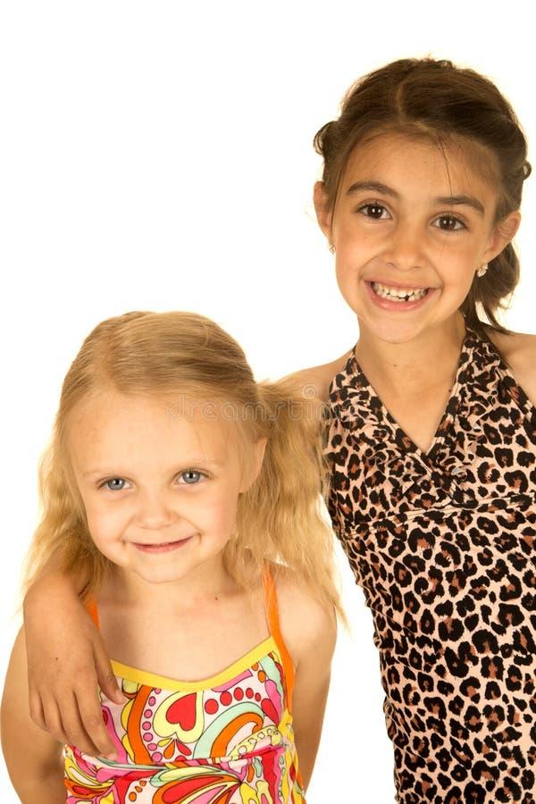 Милые маленькие девочки нося купальники смотря вперед стоковые фотографии rf