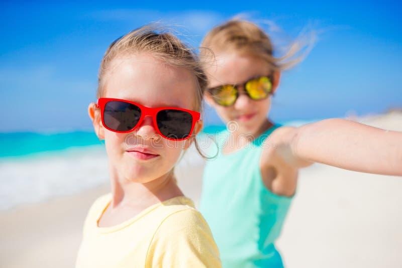 Милые маленькие девочки принимая selfie на тропический пляж на экзотическом острове во время летних каникулов стоковая фотография