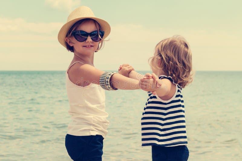 Милые маленькие девочки (сестры) танцуя на пляже стоковое фото