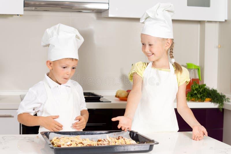 Милые маленькие ребеята сделали пиццу на белой таблице стоковое фото rf