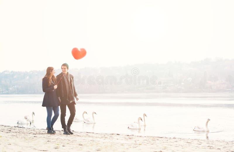 Милые молодые пары в влюбленности, идя на берег реки, с красным воздушным шаром стоковое изображение