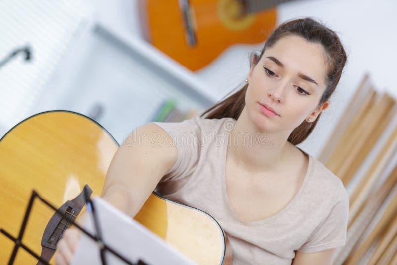 Милые ноты чтения брюнет и гитара играть стоковые изображения
