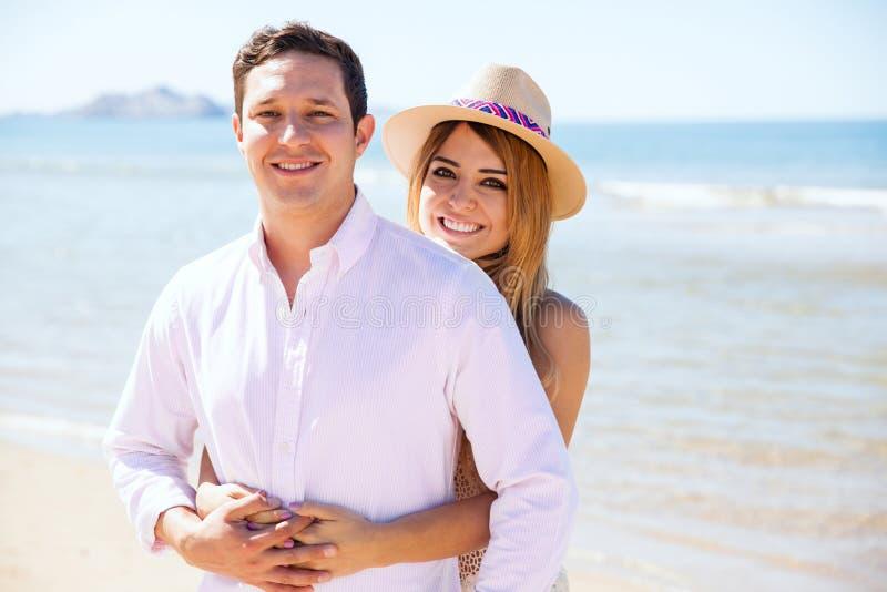 Милые пары ослабляя на пляже стоковые изображения