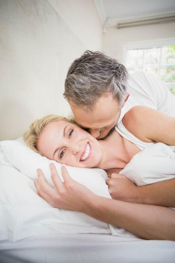 Милые пары прижимаясь в кровати стоковое фото rf