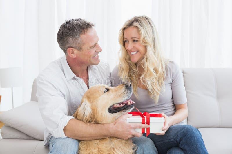 Милые пары сидя держащ подарок стоковые изображения rf