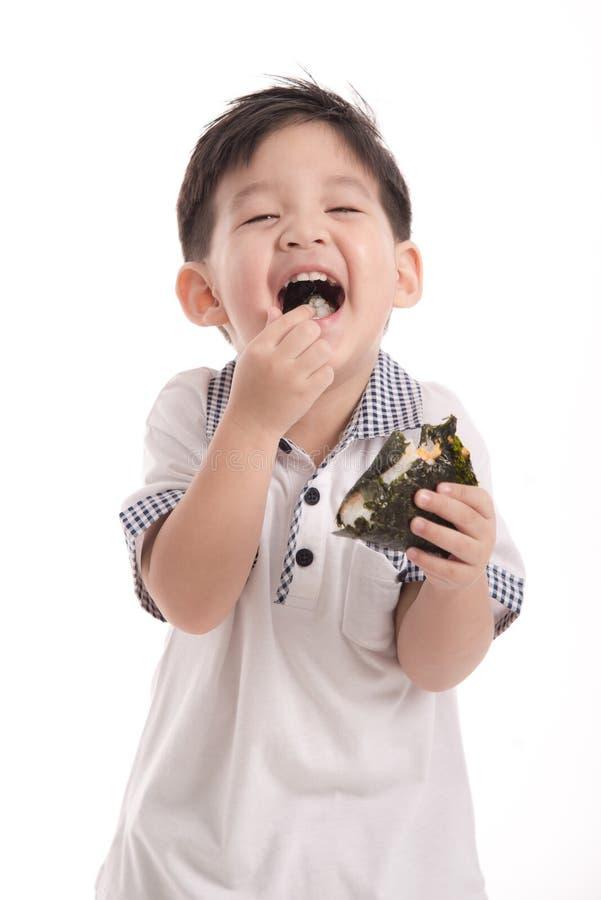 Милый азиатский ребенок есть шарик риса или onigiri стоковая фотография rf