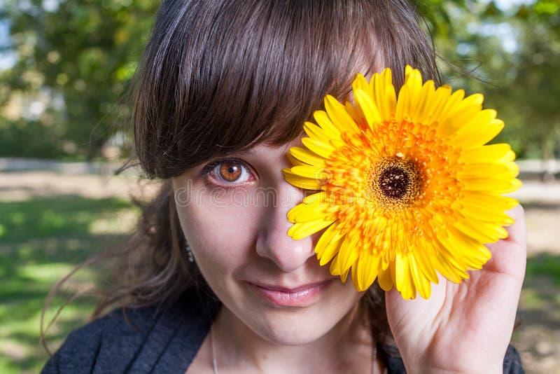 Милый глаз крышки одного женщин желтым gerbera стоковые изображения rf