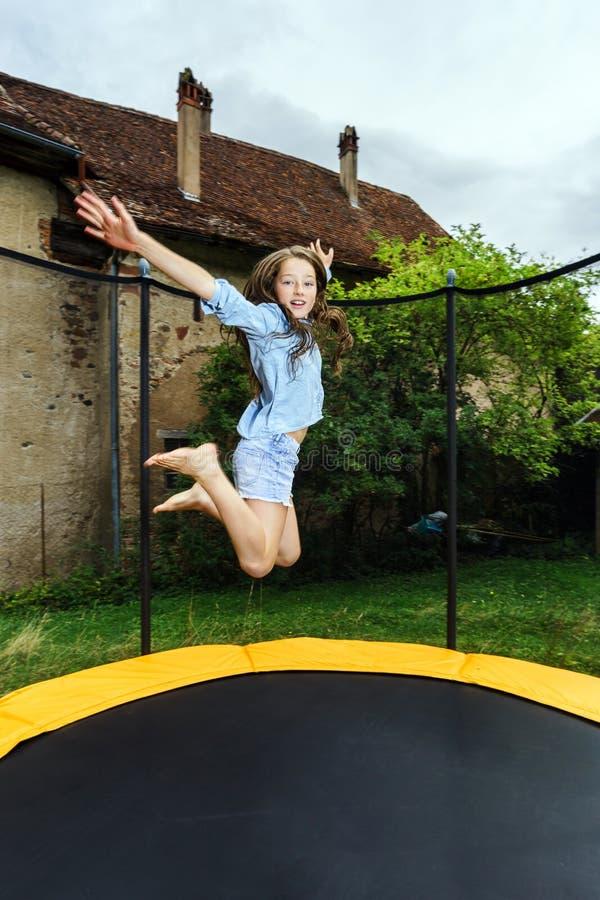 Милый девочка-подросток скача на батут стоковое изображение rf