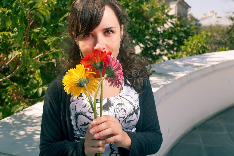 Милый женский пахнуть букет цветков outdoors стоковые фото