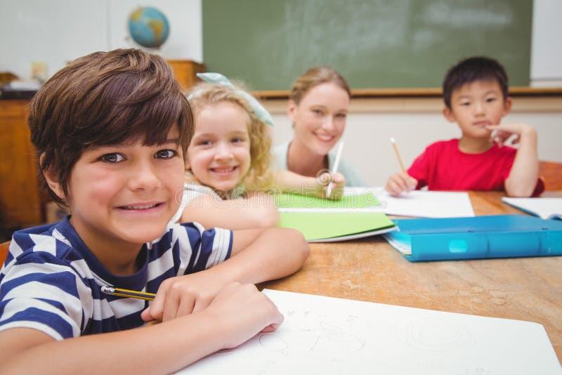 Милый зрачок порции учителя в классе усмехаясь на камере стоковые фото