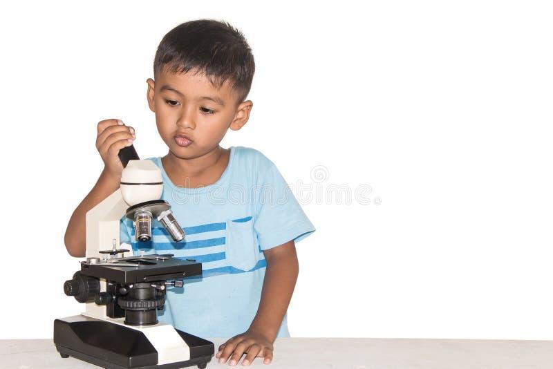 Милый маленький азиатский мальчик и микроскоп стоковые изображения