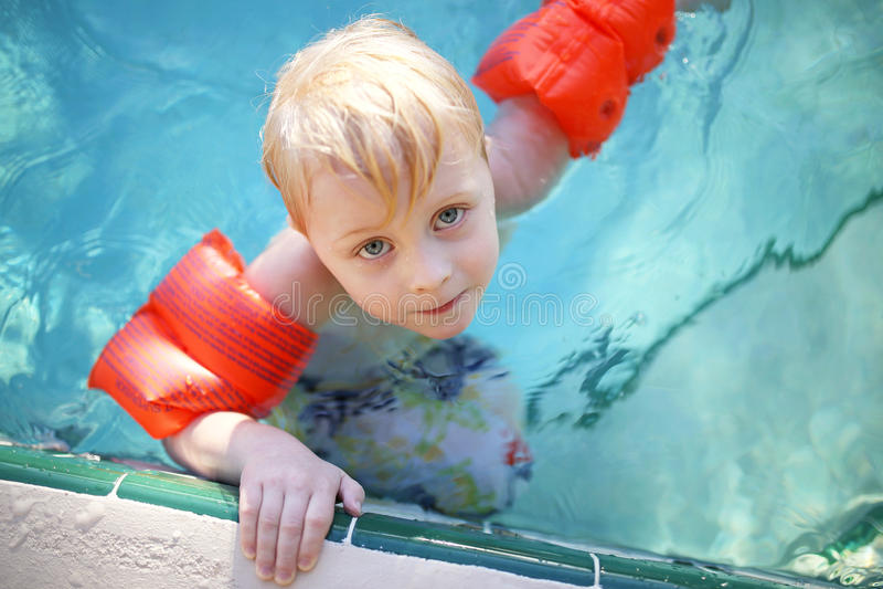 Милый маленький ребенок с рукой Floaties в бассейне стоковая фотография rf