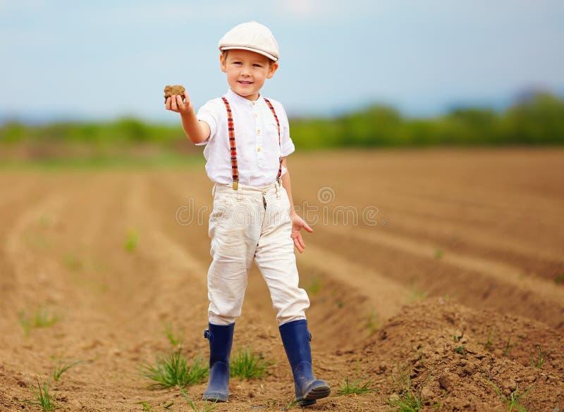 Милый маленький фермер на поле весны держа ком земли стоковые изображения rf