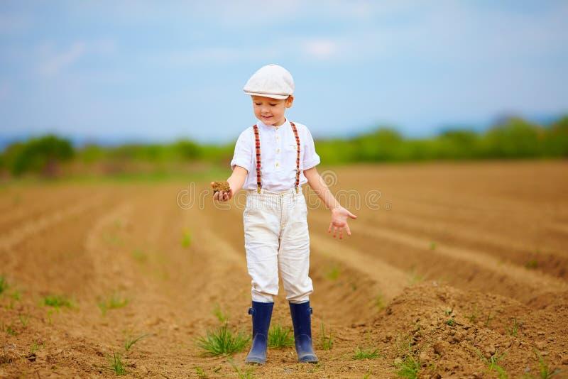 Милый маленький фермер на поле весны держа ком земли стоковая фотография rf