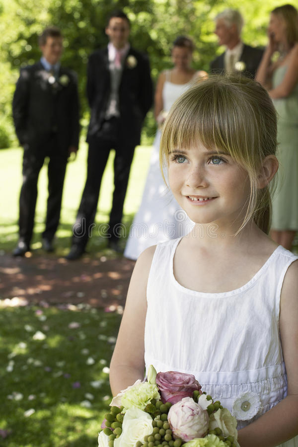 Милый маленький Bridesmaid держа букет в лужайке стоковое изображение