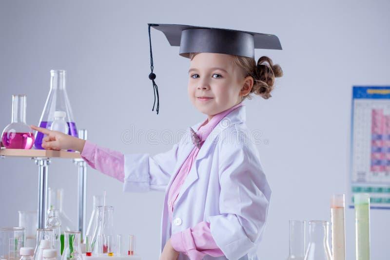Милый маленький laboratorian представлять в постдипломной шляпе стоковое фото rf