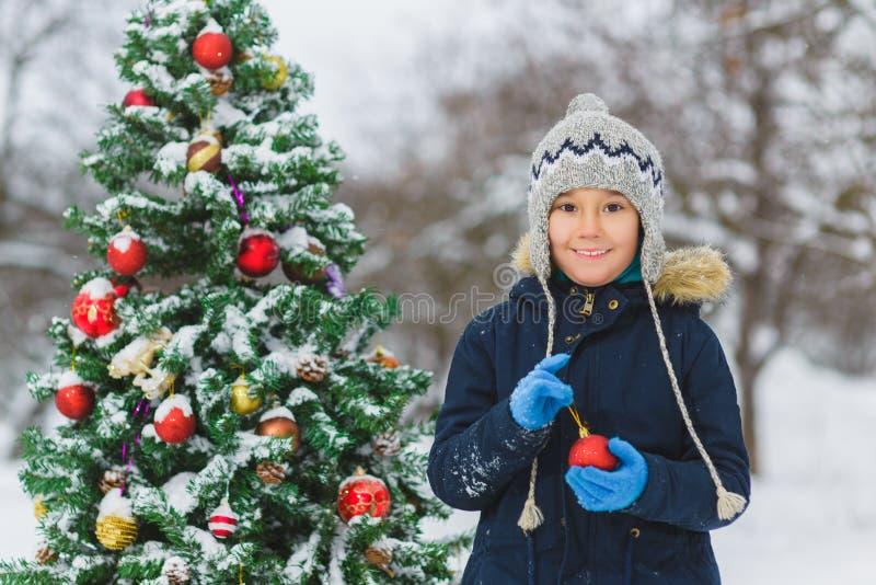 Милый маленького мальчик ребенка или preschool украшая рождественскую елку внешнюю стоковое изображение