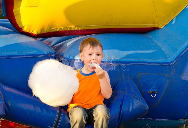 Милый малый мальчик наслаждаясь ручкой зубочистки конфеты стоковое изображение rf