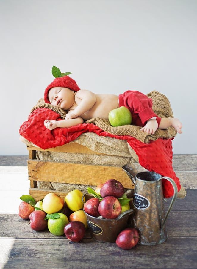 Милый малыш спать на коробке яблок стоковое изображение rf
