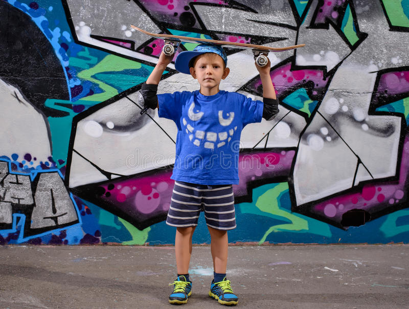 Милый мальчик балансируя скейтборд на его голове стоковые фото