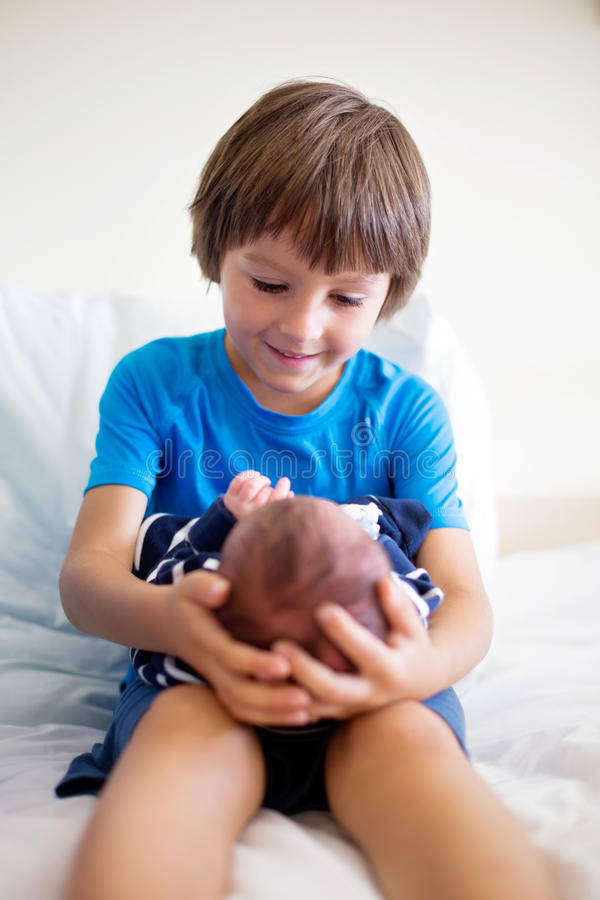 Милый мальчик, брат, встречая в первый раз его новый отвар младенца стоковая фотография rf