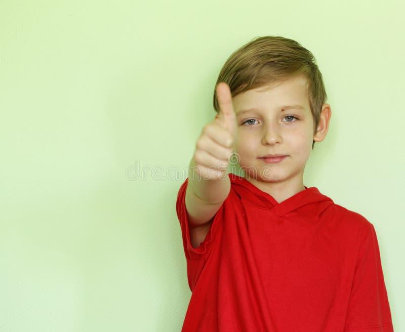 Милый мальчик в красной рубашке показывает подобие стоковое фото rf
