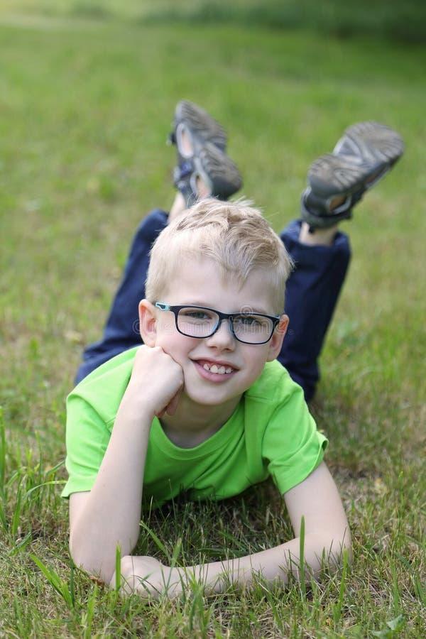 Милый мальчик лежит на траве стоковое изображение