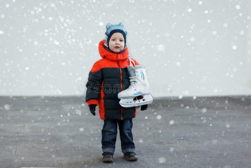Милый мальчик держит коньки нося теплые одежды g зимы стоковое изображение rf