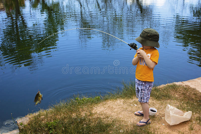 Мальчик улавливая рыбу стоковое фото