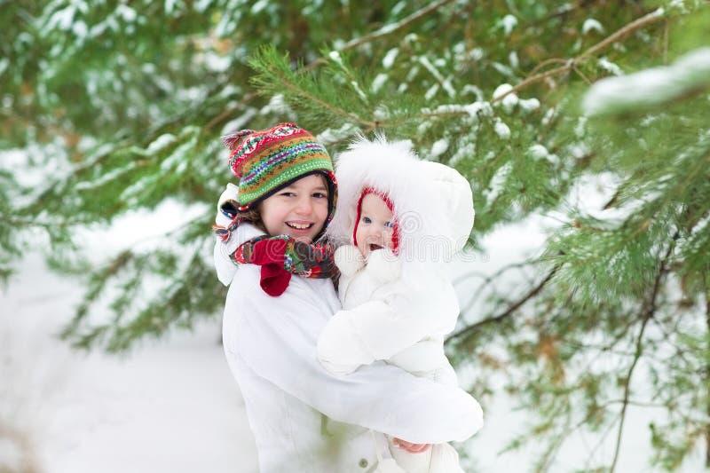 Милый мальчик обнимая его сестру младенца в парке зимы стоковое изображение rf