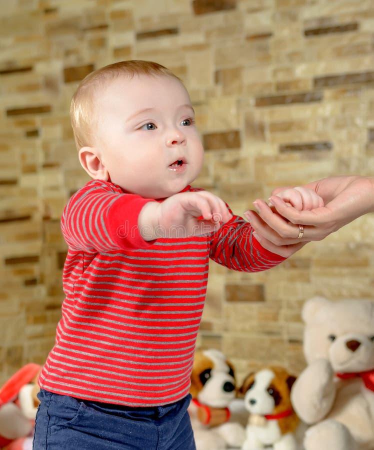 Милый мальчик предпринимая меры его первые шаги стоковая фотография