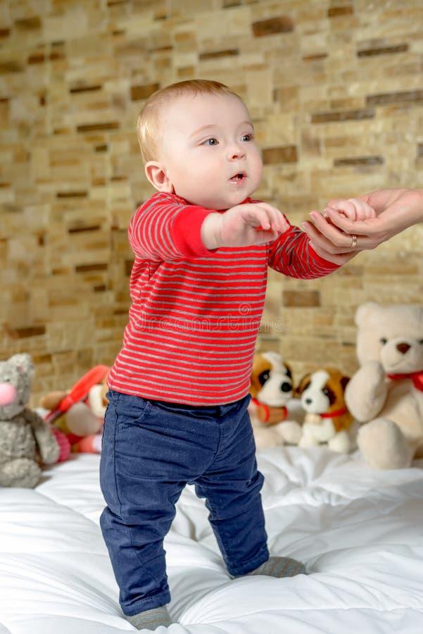 Милый мальчик предпринимая меры его первые шаги стоковые изображения