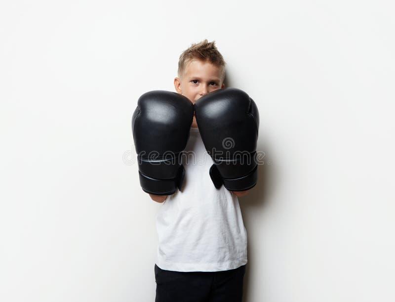 Милый мальчик стоя в перчатках бокса и ем стоковое фото rf