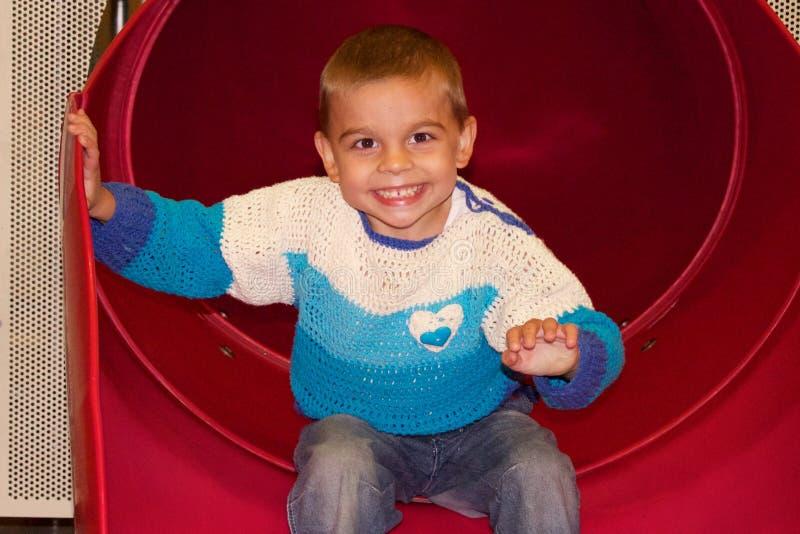 Милый мальчик усмехаясь после смещать скольжение стоковые изображения
