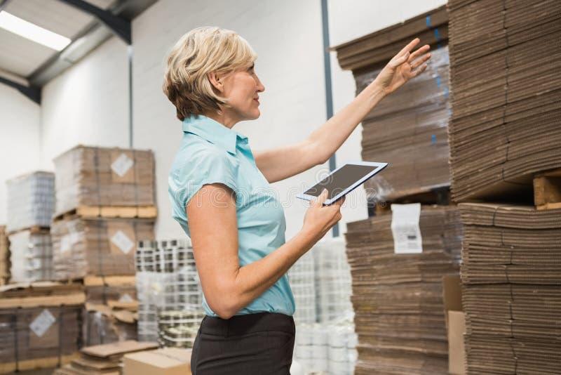 Милый менеджер склада используя ПК таблетки стоковые фото