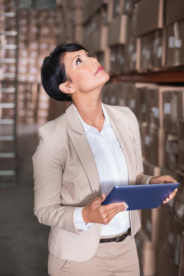 Милый менеджер склада смотря вверх держащ ПК таблетки стоковые изображения