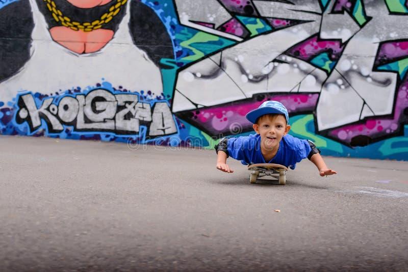 Милый молодой мальчик играя на его скейтборде стоковая фотография
