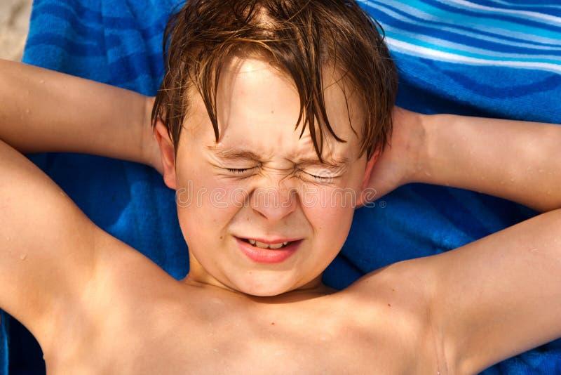 Милый молодой мальчик на пляже закрывает стоковое изображение rf