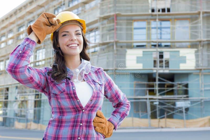 Милый молодой привлекательный женский рабочий-строитель нося трудную шляпу и стоковое фото rf